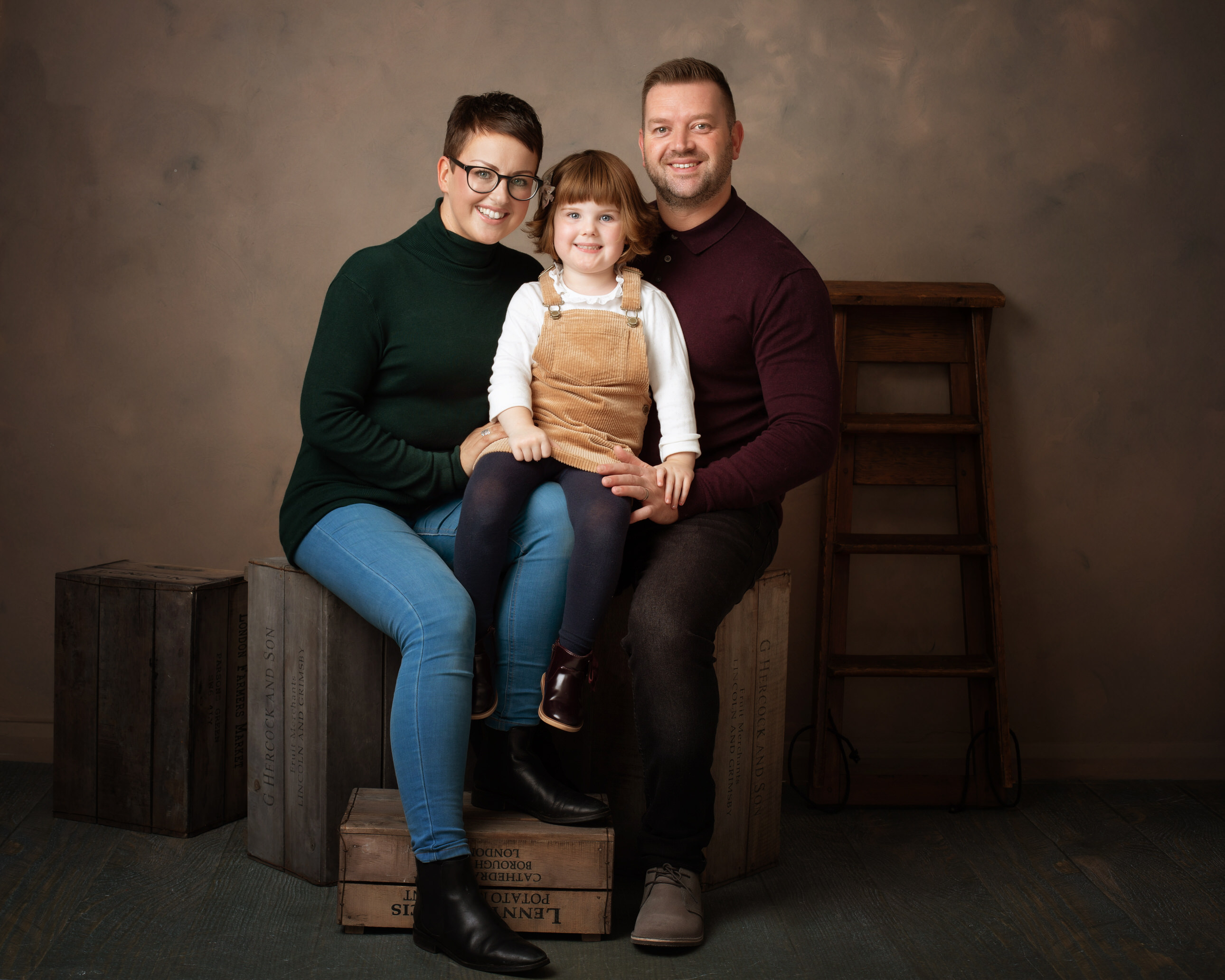 Parents with daughter in studio by Family photographer Lancashire