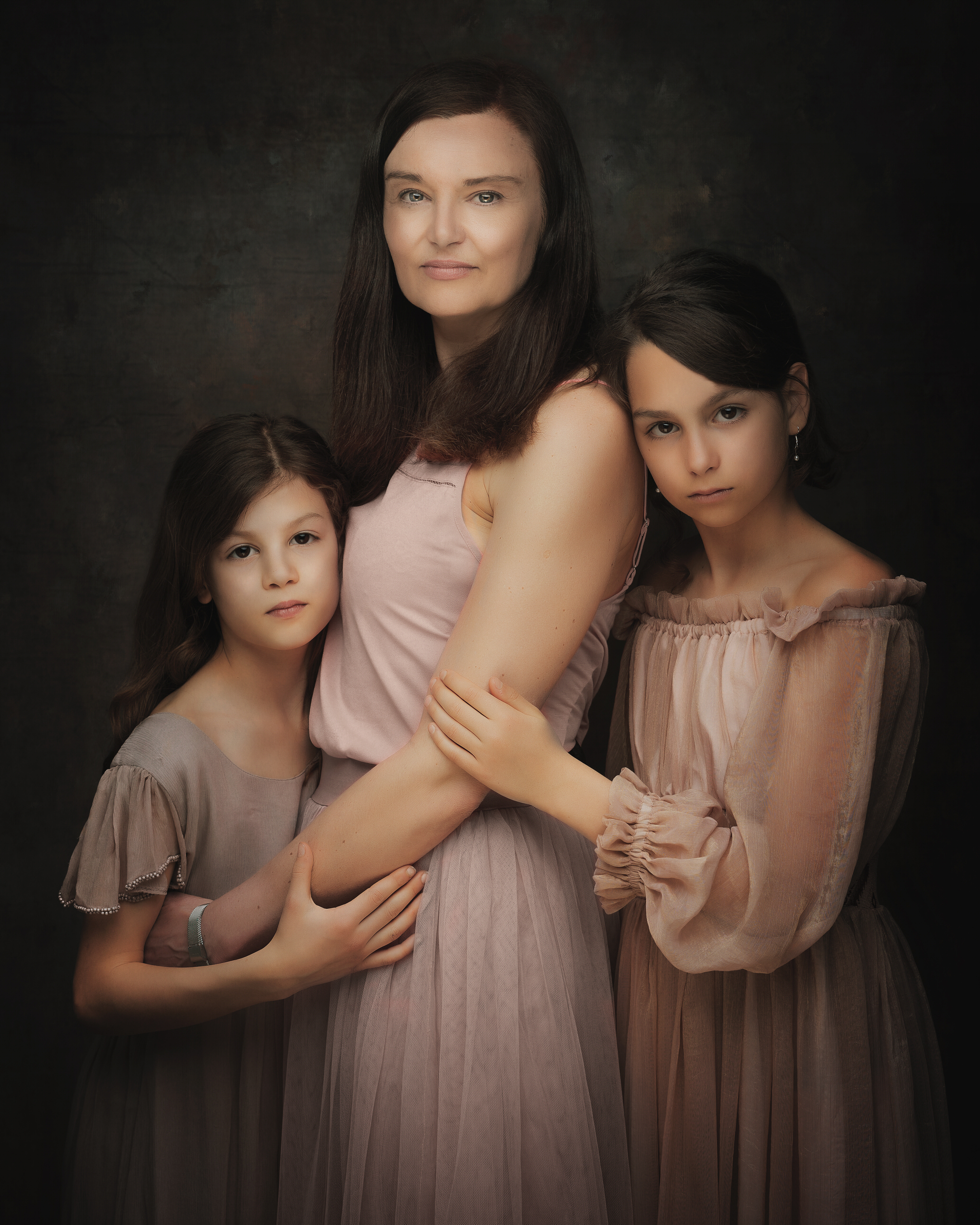 mum with daughters in fine art style studio by Family photographer Lancashire