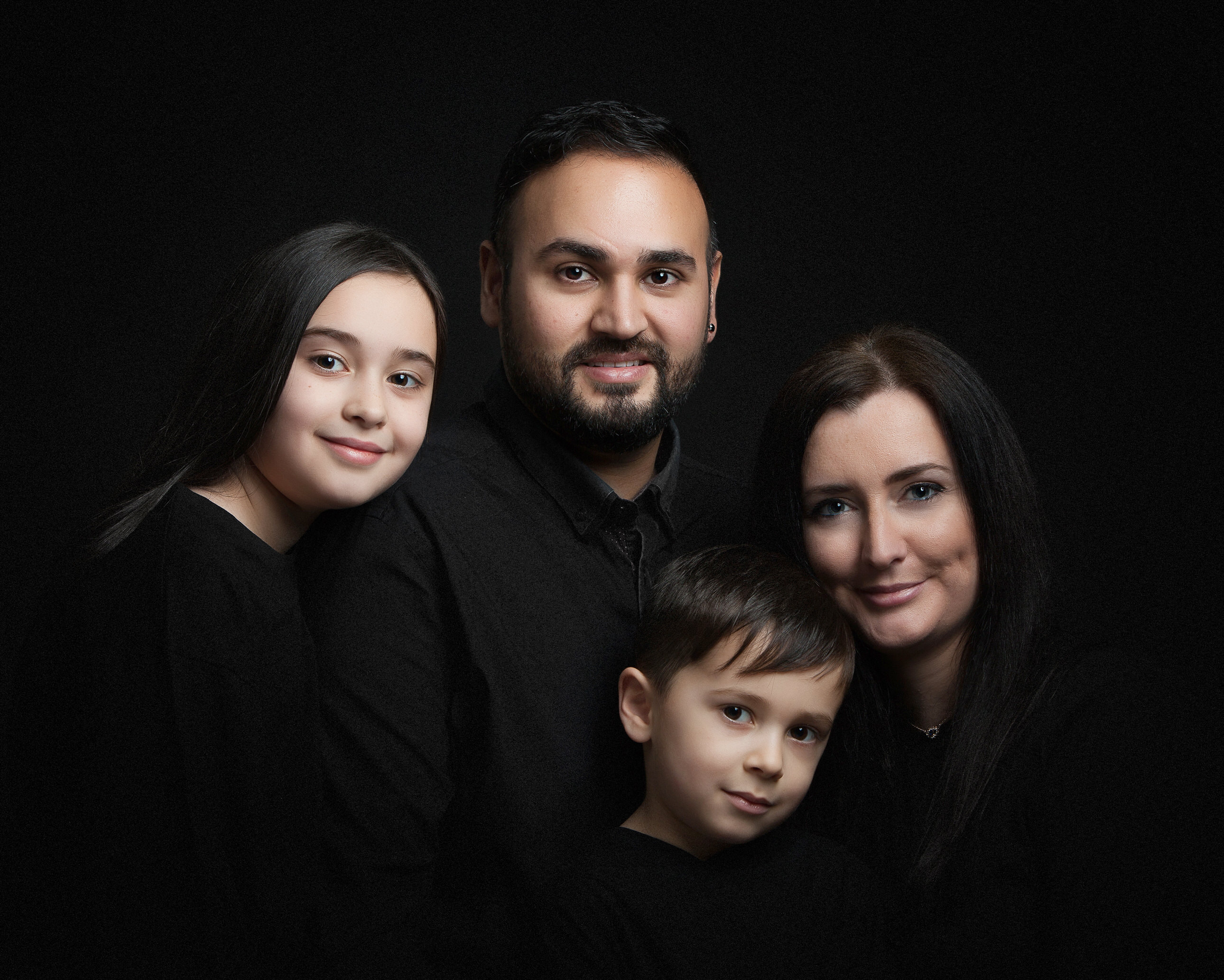 family of four on black background in studio by Family photographer Lancashire