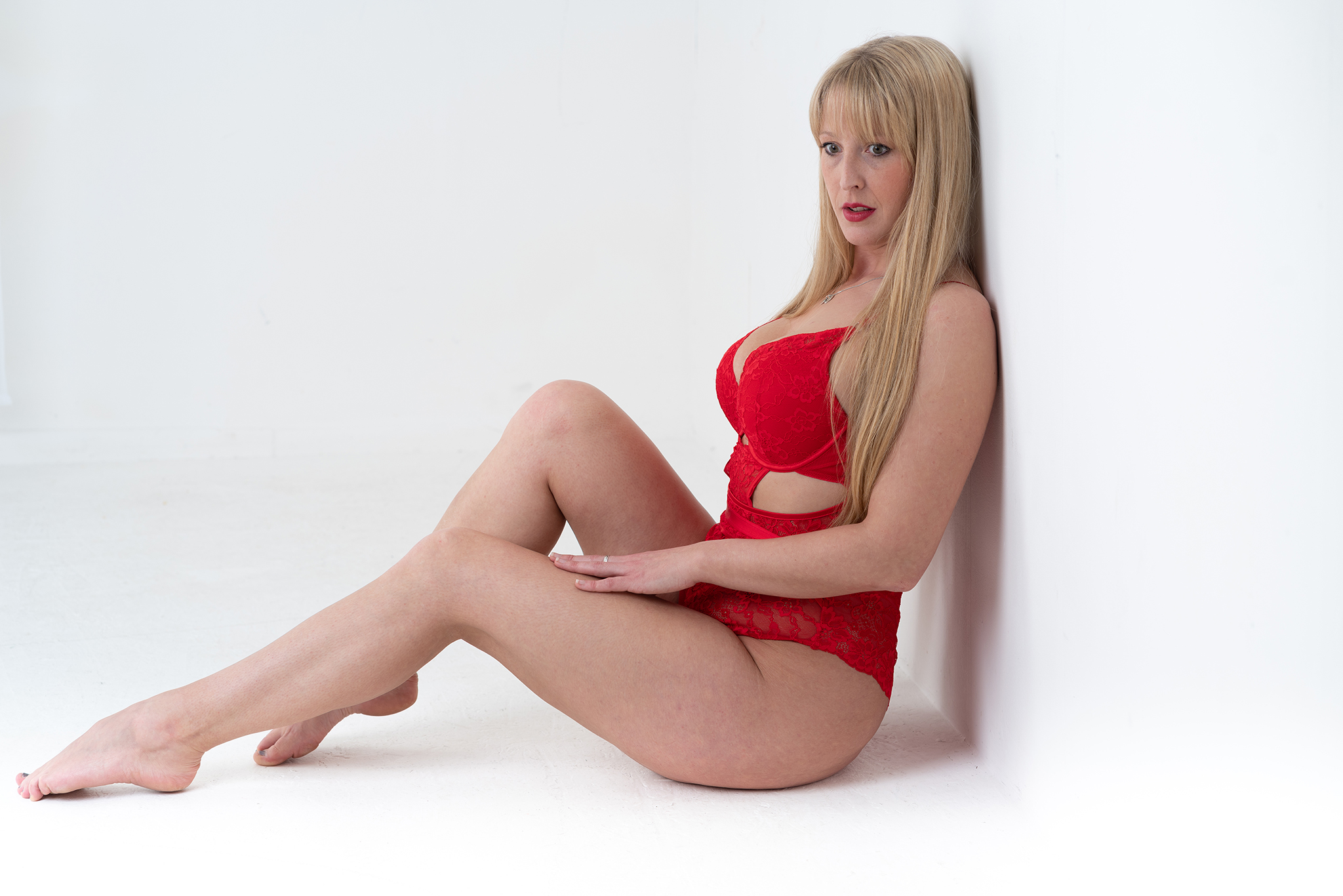 blonde model in red underwear on white background by Boudoir Photographer Lancashire