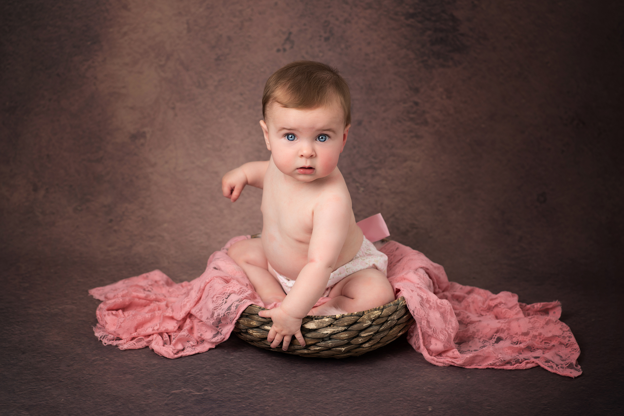 sitting baby in basket by Portrait photographer Preston