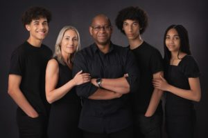 Family with teenagers photogrphed in black clothes on dark backfround by Family Photographer Preston Lancashire