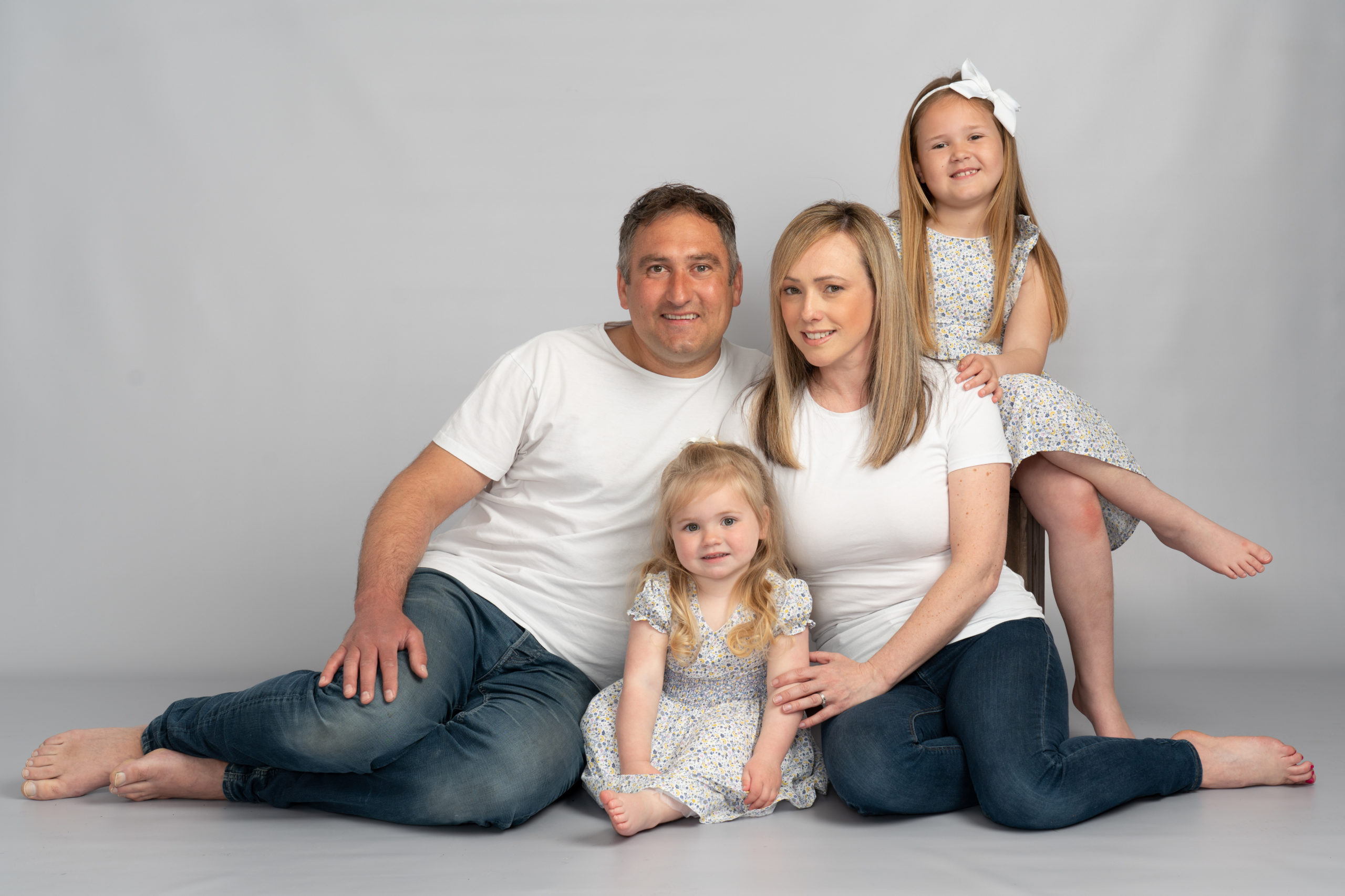 family with two young girls in white t-shirts on white background photo studio by Family photographer in preston lancashire