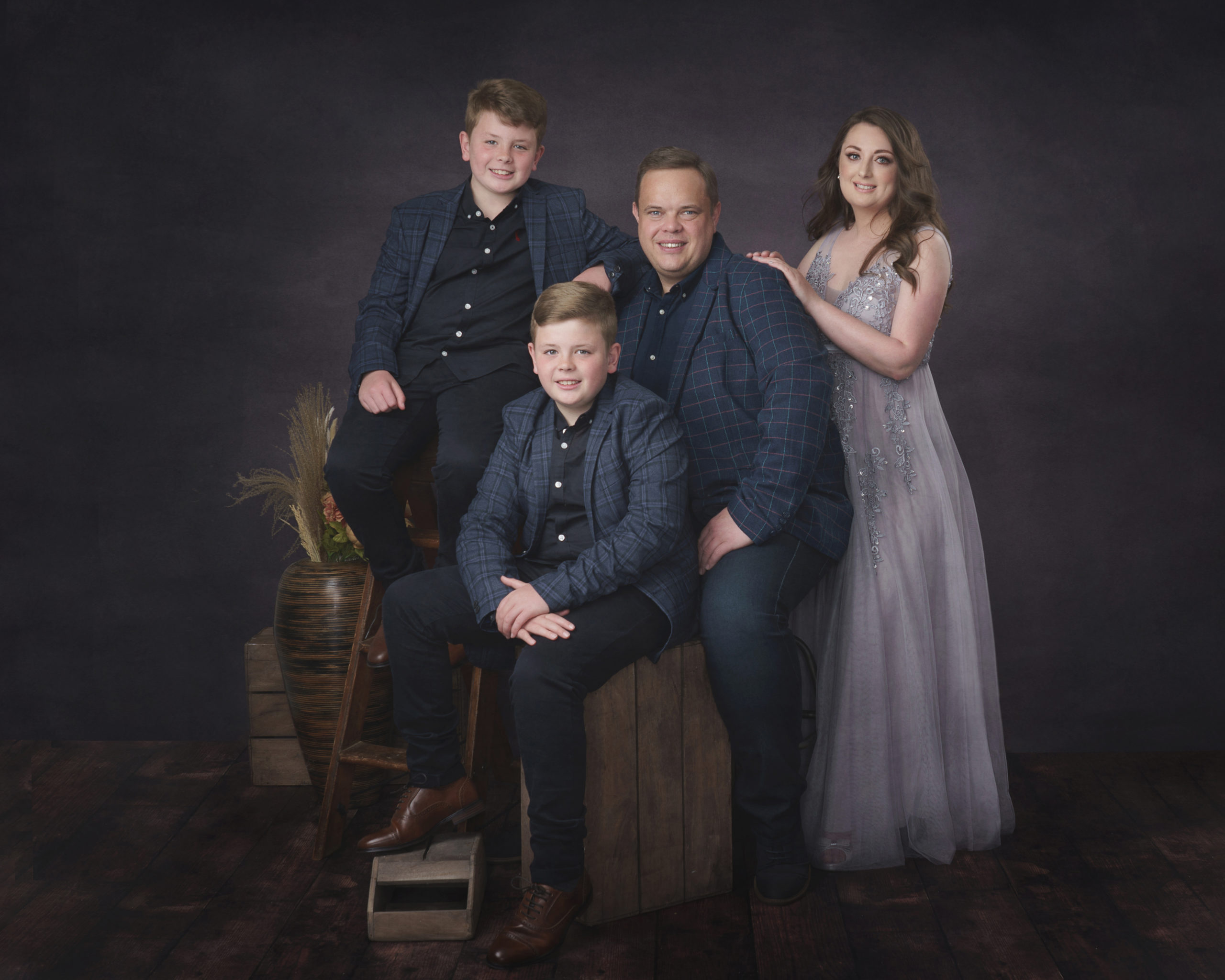 family with two boys in dark background photography studio by Family photographer in preston lancashire