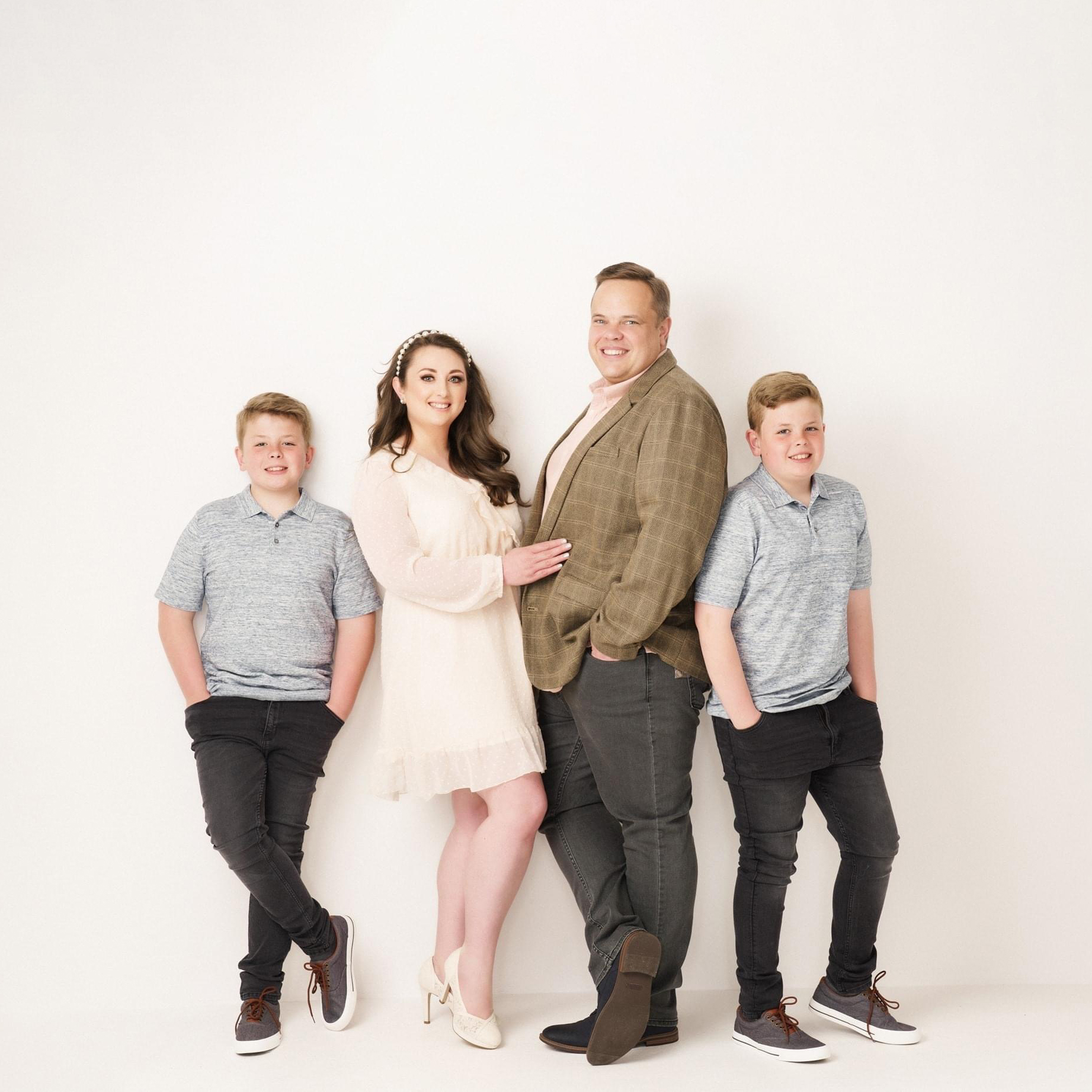 family of four in photography studio on white background by Family photographer in preston lancashire