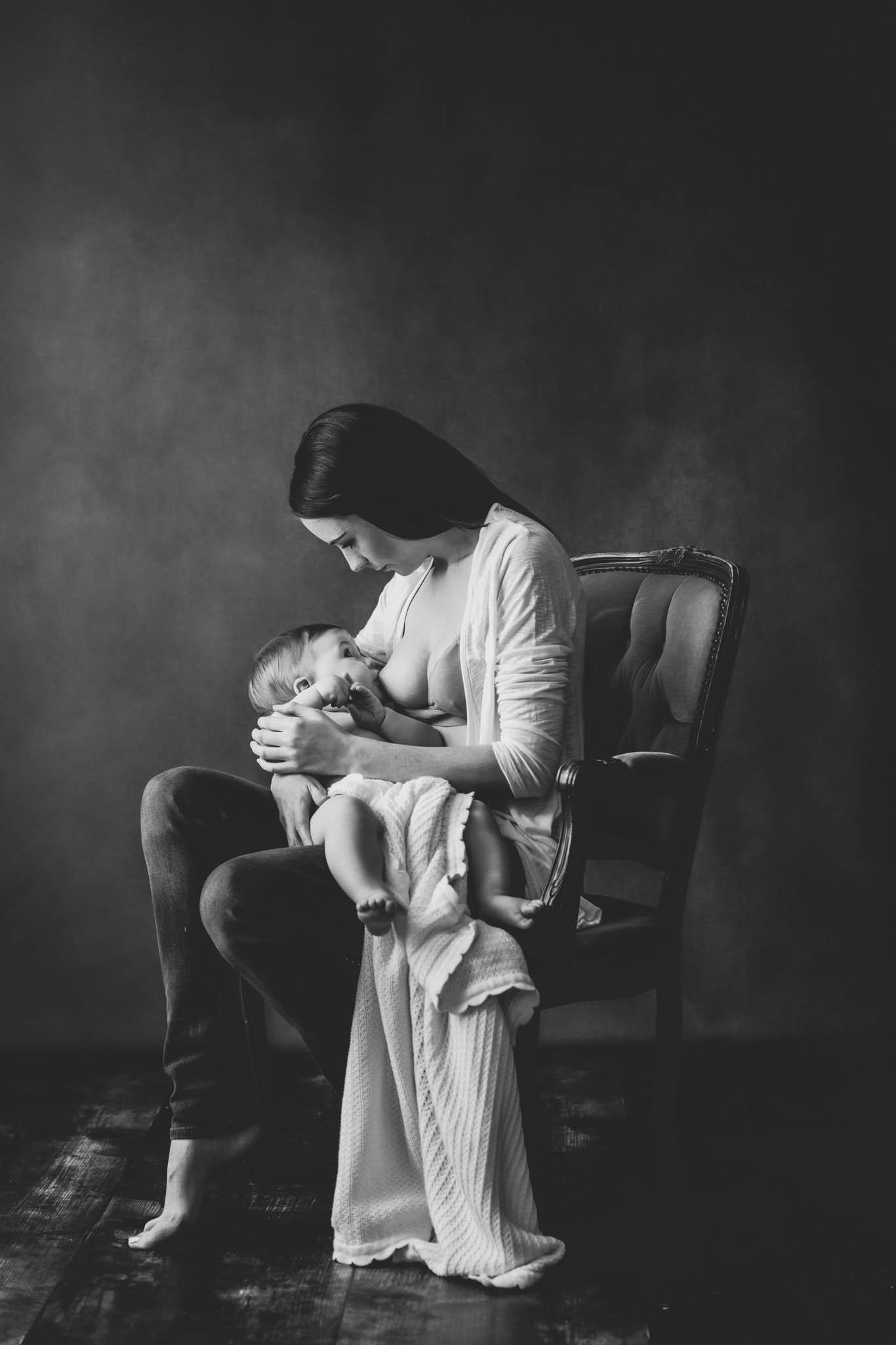 black and white portrait of mum breastfeeding baby girl on grey background by Family photographer Lancashire